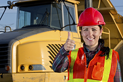 A royalty free image from the construction industry of a positive white collar construction engineer giving the thumbs up signal to show success. The worker is smiling and friendly standing in front of construction machinery which is a hauling truck. She is wearing safety glasses and a safety vest.